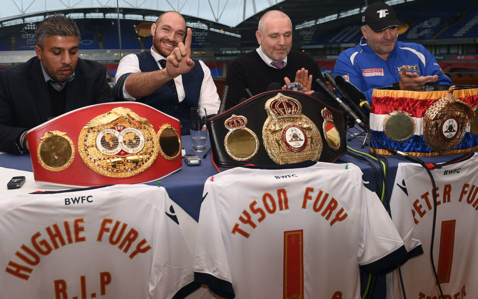 """(FILES) This file photo taken on November 30, 2015 shows (L-R) Asif Vali, Britain's world heavyweight champion Tyson Fury, trainer and uncle Peter Fury and father John Fury take part in a press conference in Bolton, north west England. Tyson Fury has given up his WBO and WBA world heavyweight titles """"with immediate effect"""" to concentrate on his """"medical treatment and recovery"""", said a statement released on October 12, 2016, by his promoters Hennessy Sports. The British boxer has admitted taking cocaine to deal with depression and was set to be stripped of his titles after cancelling two planned rematches this year against Ukrainian former champion Wladimir Klitschko. / AFP PHOTO / PAUL ELLIS"""