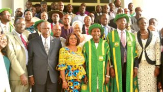 Dr. Onu (3rd from right) in convocation grown, the wife (4th from right), and UNN VC, Prof. Benjamin Ozumba (2nd from right) flanked by officials of UNN Founder's Day committee.