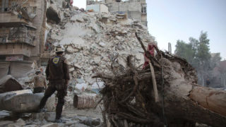 A member of the Syrian Civil Defence -- known as the White Helmets -- stands amid the rubble of a destroyed building in Aleppo, on October 17, 2016 (AFP Photo/Karam Al-Masri)