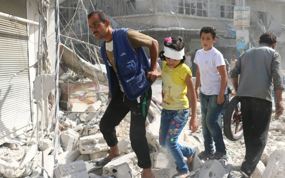 Syrians walk over rubble following air strikes on the rebel-held Fardous neighbourhood of the northern embattled Syrian city of Aleppo on October 12, 2016. / AFP PHOTO / AMEER ALHALBI