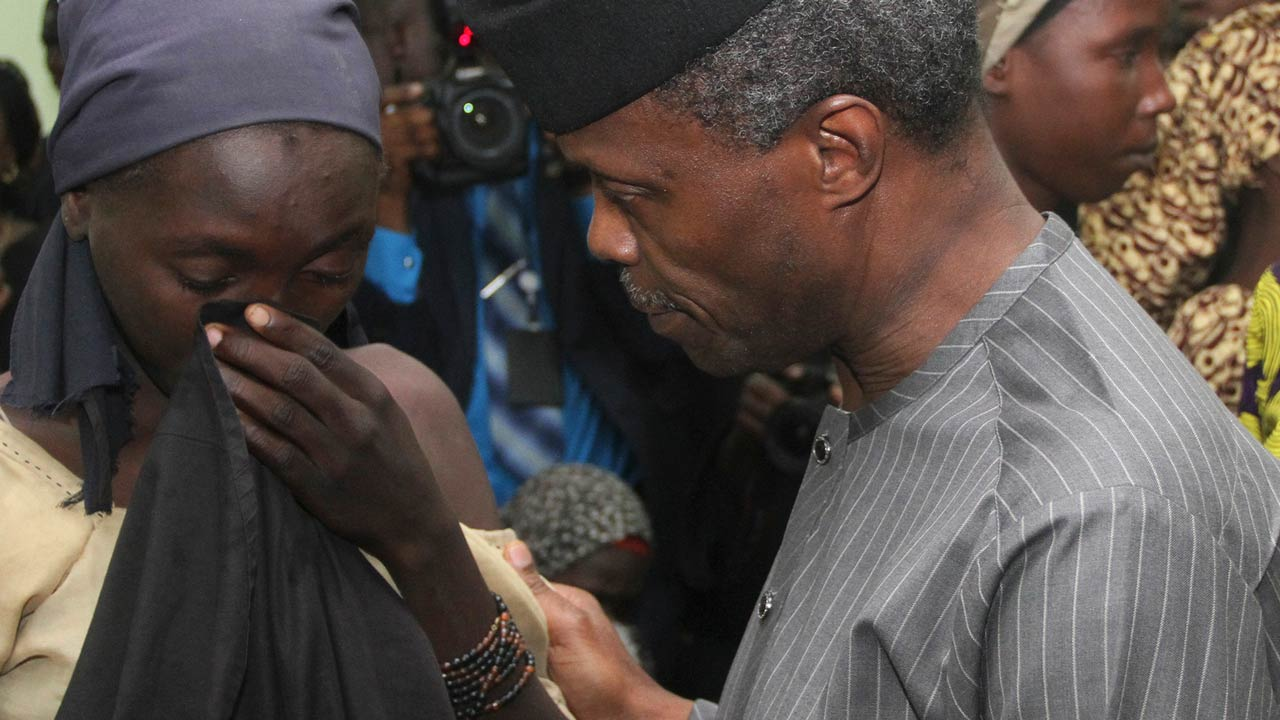 One of the 21 freed Chibok girls wipes away her tears as Nigerian Vice President Yemi Osinbajo tries to comforts her at his office in Abuja on October 13, 2016. Jihadist group Boko Haram has freed 21 of the more than 200 Chibok schoolgirls kidnapped more than two years ago, raising hopes for the release of the others, officials said Thursday. Local sources said their release was part of a prisoner swap with the Nigerian government, but the authorities denied doing a deal with Boko Haram. PHOTO: PHILIP OJISUA / AFP