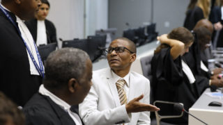 """Narcisse Arido (C) of the Central African Republic talks with his lawyer in the courtroom of the International Criminal Court (ICC) in The Hague, on October 19, 2016.  International judges on October 19, 2016 found former Congolese vice president Jean-Pierre Bemba and four aides guilty of corrupting witnesses, by bribing them with money and laptops to lie during the testimony to his war crimes trial. The case was """"about clear, and downright criminal behaviour of the five accused... that resulted in serious offences against the administration of justice,"""" judge Bertram Schmitt told the International Criminal Court as handed down the verdict.   / AFP PHOTO / POOL / Michael Kooren / Netherlands OUT"""