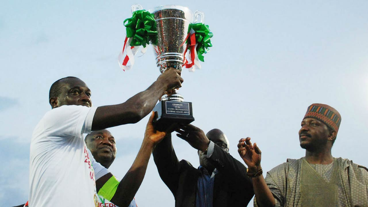 Rangers Captain, Okey Odita (left), receiving the 2015/2016 league trophy from Governor Ifeanyi Ugwuanyi (second left), NFF President, Amaju Pinnick and LMC Chairman, Shehu Dikko after the final game of the season in Enugu…recently.                            PHOTO: LMC