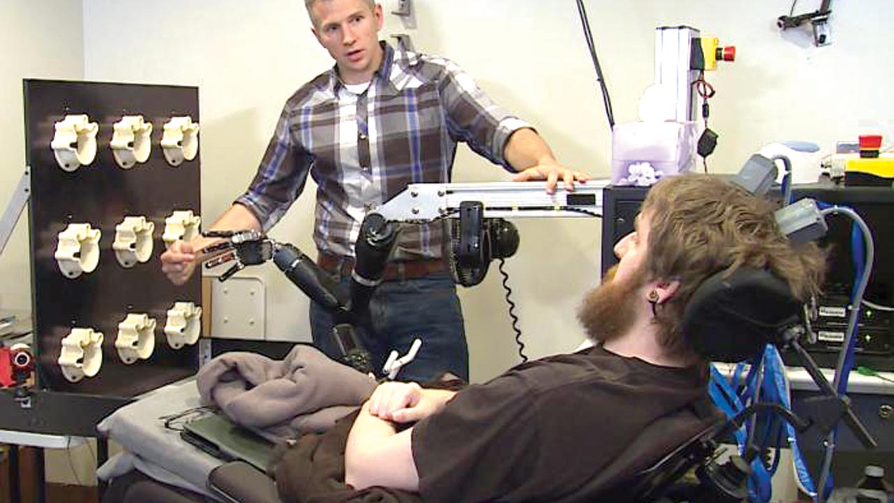 Nathan Copeland - pictured with lead researcher Dr. Robert Gaunt - has regained sense of touch as a result of a brain implant and a robotic arm. Image credit: UPMC/Pitt Health Sciences
