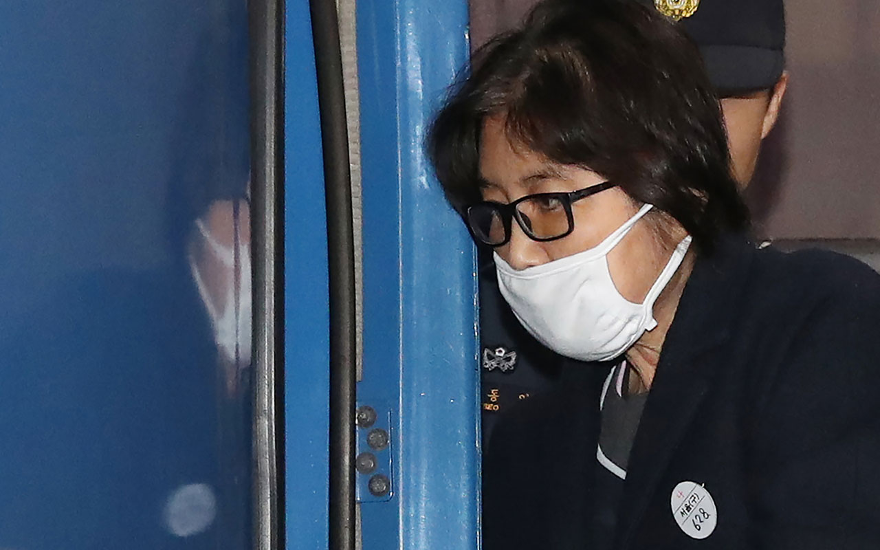 "This picture taken on November 19, 2016 shows Choi Soon-Sil, the woman at the heart of a lurid political scandal engulfing South Korea's President Park Geun-Hye, being escorted after questioning at the Seoul Central District Prosecutors' Office in Seoul. Park had a ""considerable"" role in a corruption and influence-peddling scandal engulfing her government, Seoul prosecutors said on November 20, as they formally laid out charges against Choi, Park's close confidante, and two former presidential aides. / AFP PHOTO / YONHAP / YONHAP /  - South Korea OUT /"