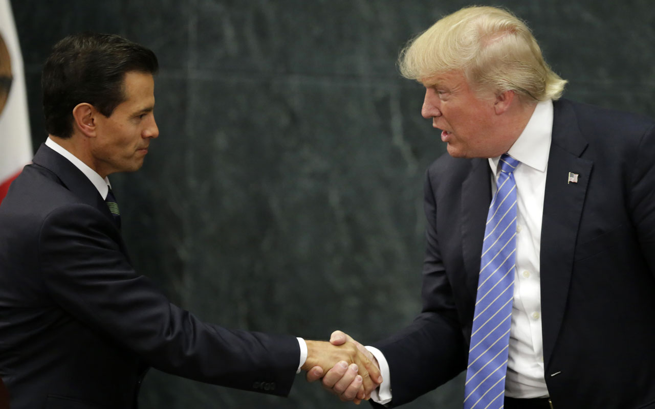"""(FILES) This file photo taken on August 31, 2016 shows Mexican President Enrique Pena Nieto (L) and US presidential candidate Donald Trump shaking hands after a meeting in Mexico City. Donald Trump said on November 9, 2016 he would bind the nation's deep wounds and be a president """"for all Americans,"""" as he praised his defeated rival Hillary Clinton for her years of public service. / AFP PHOTO / YURI CORTEZ"""