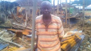 Chief Bassey in front of his burnt house