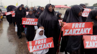 Northern Nigerian city of Kano shows protesters from the pro-Iranian Islamic Movement in Nigeria (IMN) marching in the rain through the streets to press for the release of their leader Ibrahim Zakzaky and his wife Zeenat. Northern Nigeria, already devastated by Boko Haram Islamist group attacks, slides into another conflict, with Iran and Saudi Arabia waging war remotely on its territory through the Izala and IMN groups, AFP reported on November 5, 2016.     / AFP PHOTO / AMINU ABUBAKAR