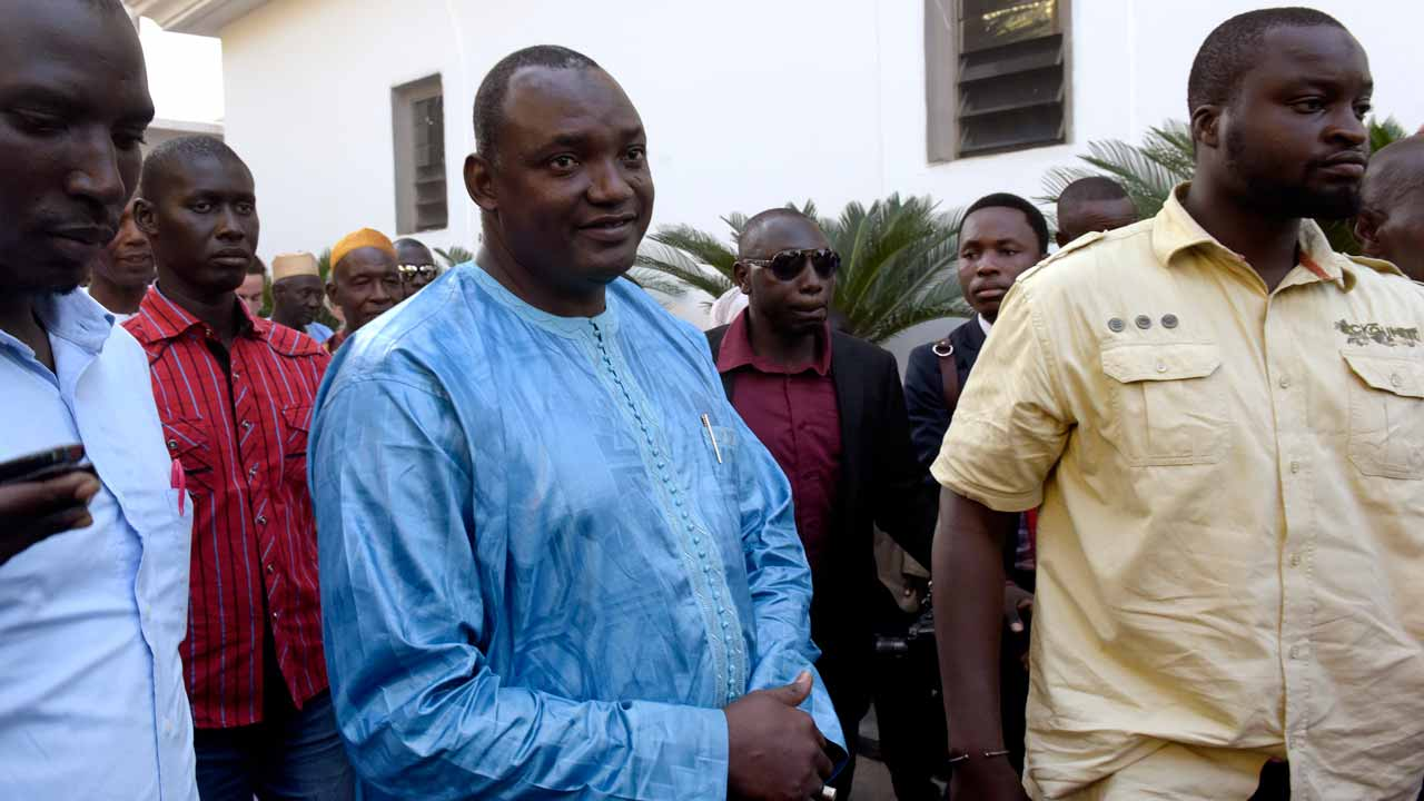 Gambian president-elect Adama Barrow (C), flanked by his supporters, arrive at a luxury hotel in Banjul, for a meeting with four African heads of state on December 13, 2016. Four African heads of state landed in The Gambia today with a mission to persuade President Yahya Jammeh to leave office, as the country's election commission was locked down by police. Jammeh's party has vowed to challenge the result of a presidential election in court, unleashing an avalanche of calls at home and abroad for him to cede power to opponent Adama Barrow, who was officially declared the winner. PHOTO: SEYLLOU / AFP
