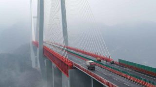 This picture taken on December 29, 2016 shows vehicles making their way through the Beipanjiang Bridge, near Bijie in southwest China's Guizhou province. The world's highest bridge has opened to traffic in China, connecting two southwestern provinces and reducing travel time by three quarters, local authorities said on December 30. STR / AFP
