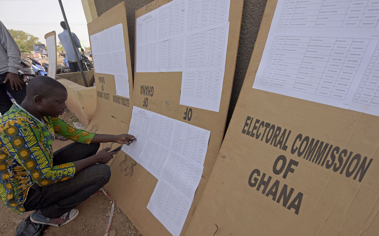 A man checks the list of names displayed at the headquarters of the Electoral Commission in Tamale on December 6, 2016 on the eve of Ghana's presidential and parliamentary elections. / AFP PHOTO / PIUS UTOMI EKPEI