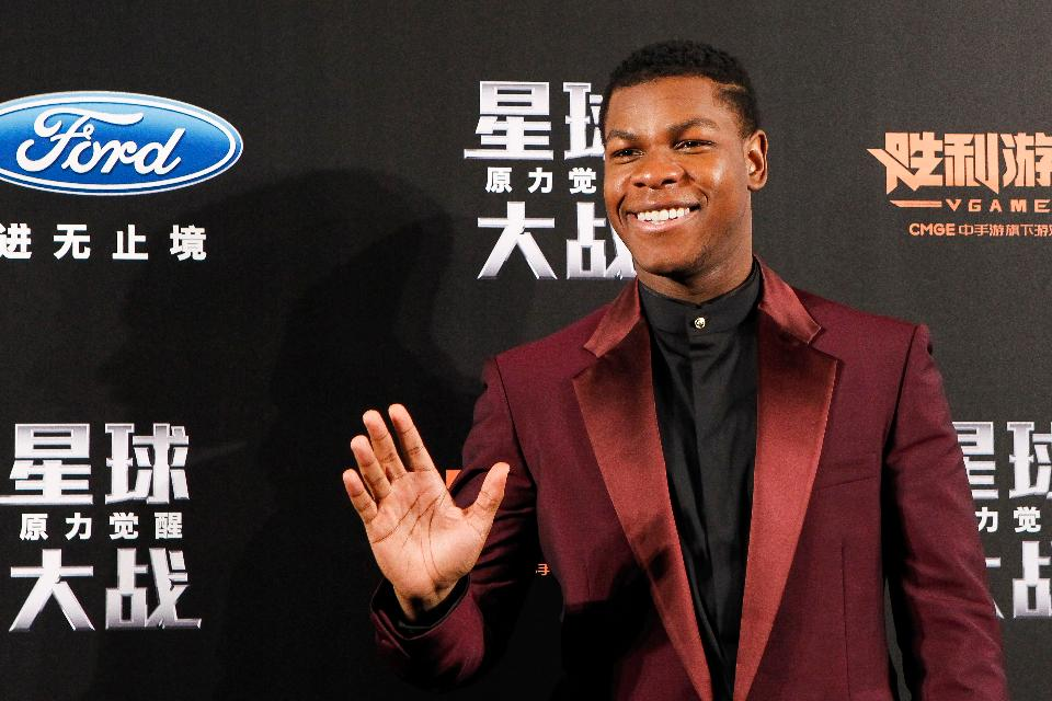 British actor John Boyega waves to fans on the stage during the premiere of 'Star Wars: The Force Awakens' on December 27, 2015 in Shanghai, China. / AFP / STR (PHOTO: STR/AFP/Getty Images