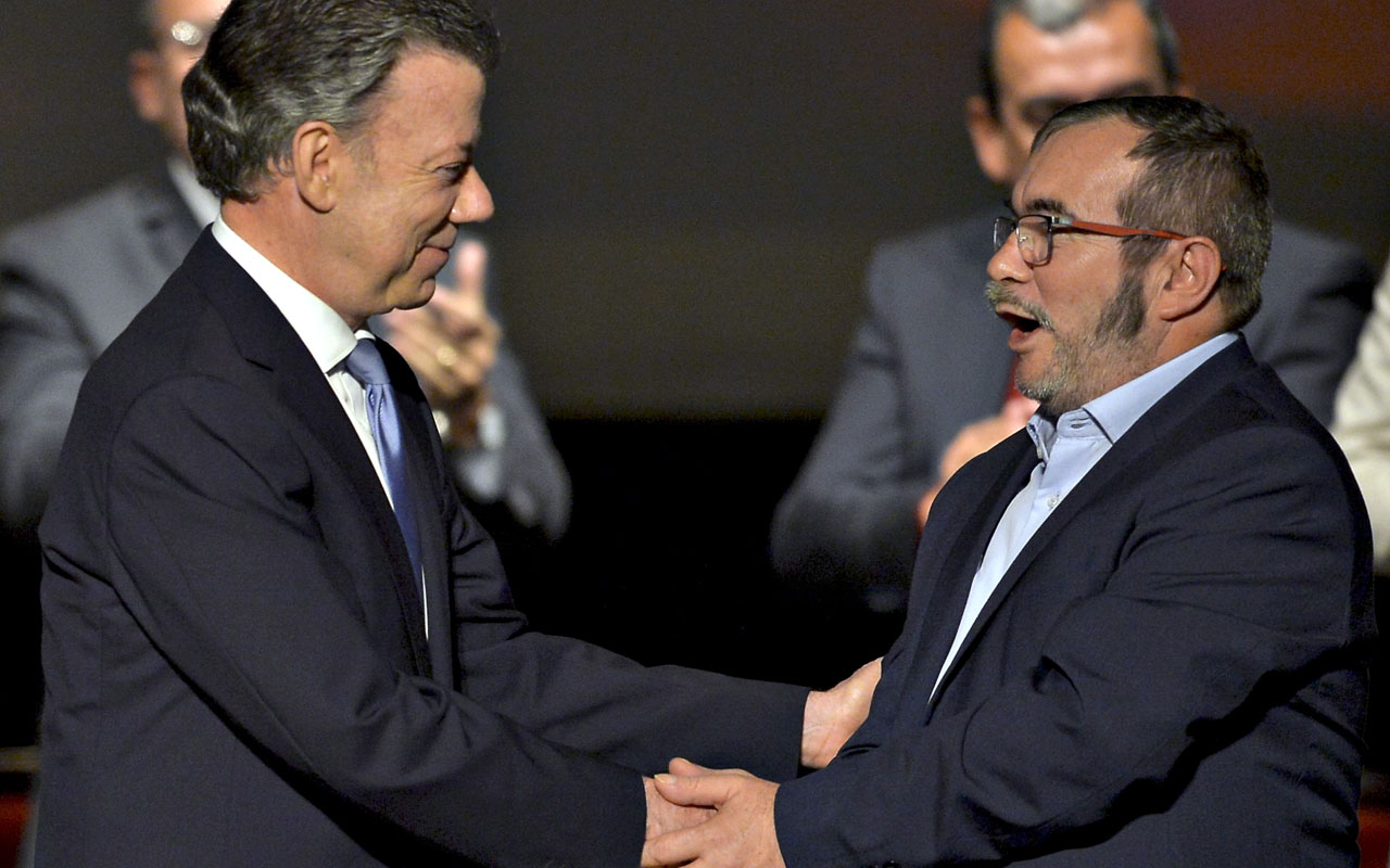 Colombian President Juan Manuel Santos (L) and FARC leader Timoleon Jimenez, aka Timochenko shake hands during the second signing of the peace agreement between the Colombian government and the FARC, at the Colon Theater in Bogota, Colombia, on November 24, 2016. Colombia's government and FARC rebels signed a controversial revised peace accord Thursday to end their half-century conflict, set to be ratified in Congress despite bitter criticism from opponents. / AFP PHOTO / LUIS ROBAYO