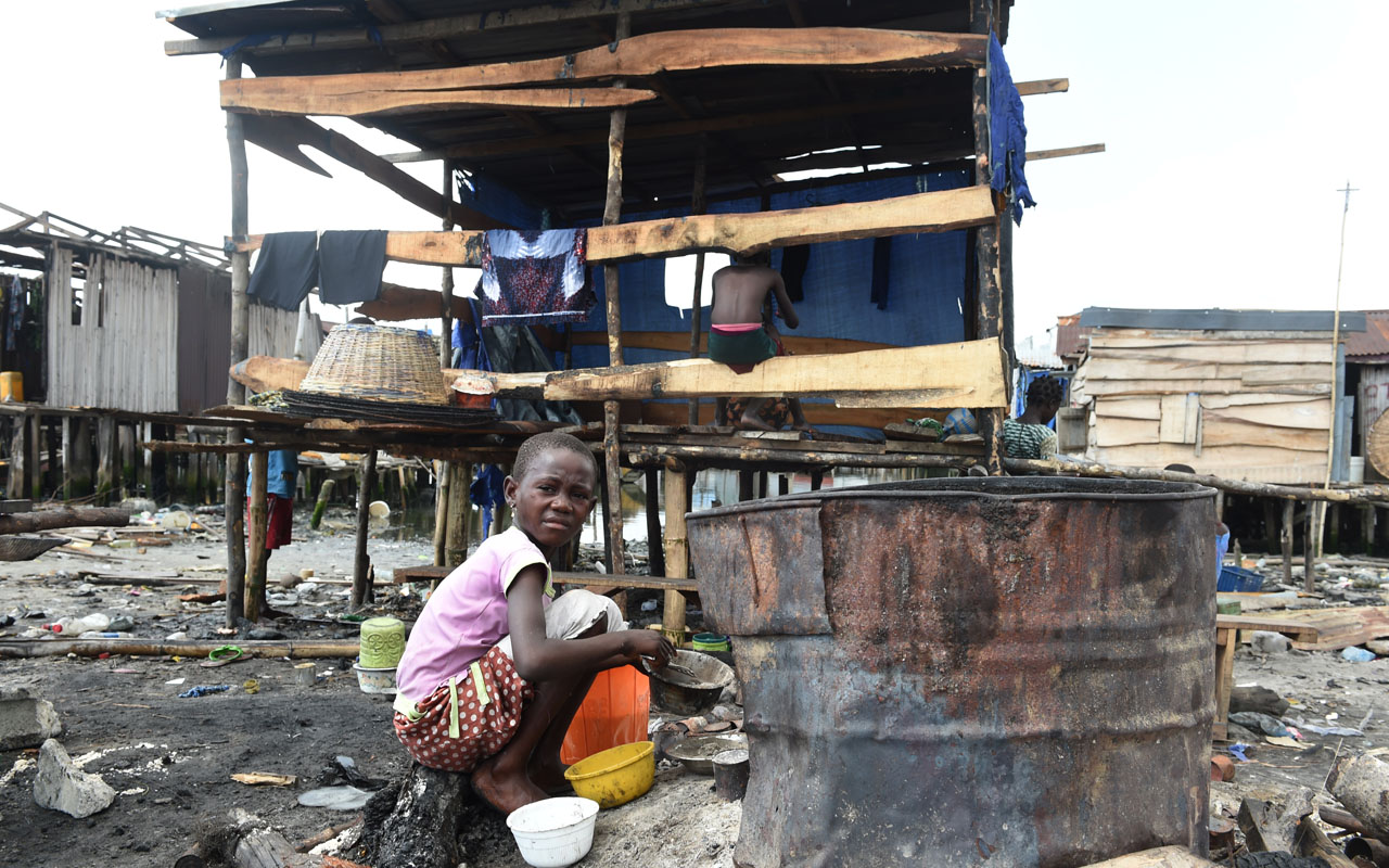 A girl sits in front of house shores at a make-shift home partly demolished at Otodo Gbame waterfront fishing communities in Lagos, on November 28, 2016. Otodo Gbame, a fishing community in Lagos is the latest casualty in a drive by the authorities to turn Nigeria's commercial capital into a megacity. Between November 9 and 11, Otodo Gbame was razed, leaving 30,000 homeless with burnt out corrugated sheets, planks and household items. / AFP PHOTO / PIUS UTOMI EKPEI