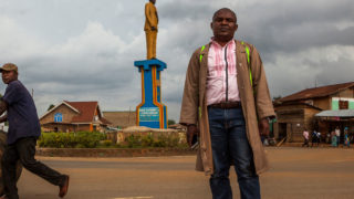 Sauveur Mulwana poses in front of one of the monuments that he created in Butembo on November 11, 2016.  Mr. Mulwana created and constructed himself a series of monuments in the city of Butembo in order to preserve the history and culture of the Nande people, the predominant ethnic group in the area. / AFP PHOTO / Eduardo Soteras /