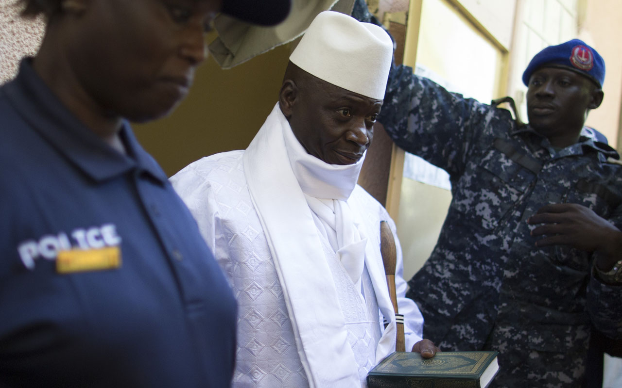 "Incumbent Gambian president Yahya Jammeh (C) leaves the polling booth after casting his marble for presidential election in a polling station, in Banjul on December 01, 2016. The first of some 880,000 eligible voters headed to polling stations despite an internet blackout imposed overnight in a nation long accused by rights groups of suppressing freedom of expression. The Gambia's unique voting system, which sees citizens vote by dropping a marble into a coloured drum for their candidate, could not be rigged, he added, meaning ""there is no reason for anybody to protest.""/ AFP PHOTO / MARCO LONGARI"