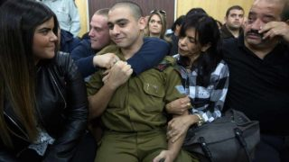 Israeli soldier Elor Azaria (C), who shot dead a wounded Palestinian assailant, sits with his parents and his girlfriend Orel (L) as he awaits for the verdict in his case at the military court in Tel Aviv on January 4, 2017. Azaria, has been on trial for manslaughter in a military court since May, with right-wing politicians defending him despite top army brass harshly condemning the killing. PHOTO: Heidi Levine / POOL / AFP