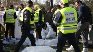 Israeli police forensic experts examine a body of one of the four Israeli soldiers killed when a Palestinian truck driver ran over a group of soldiers at the Jerusalem promenade on January 8, 2017. A Palestinian rammed a truck into a group of Israeli soldiers visiting a popular tourist spot in Jerusalem, killing four and wounding at least 15 people, authorities said.  Gali TIBBON / AFP