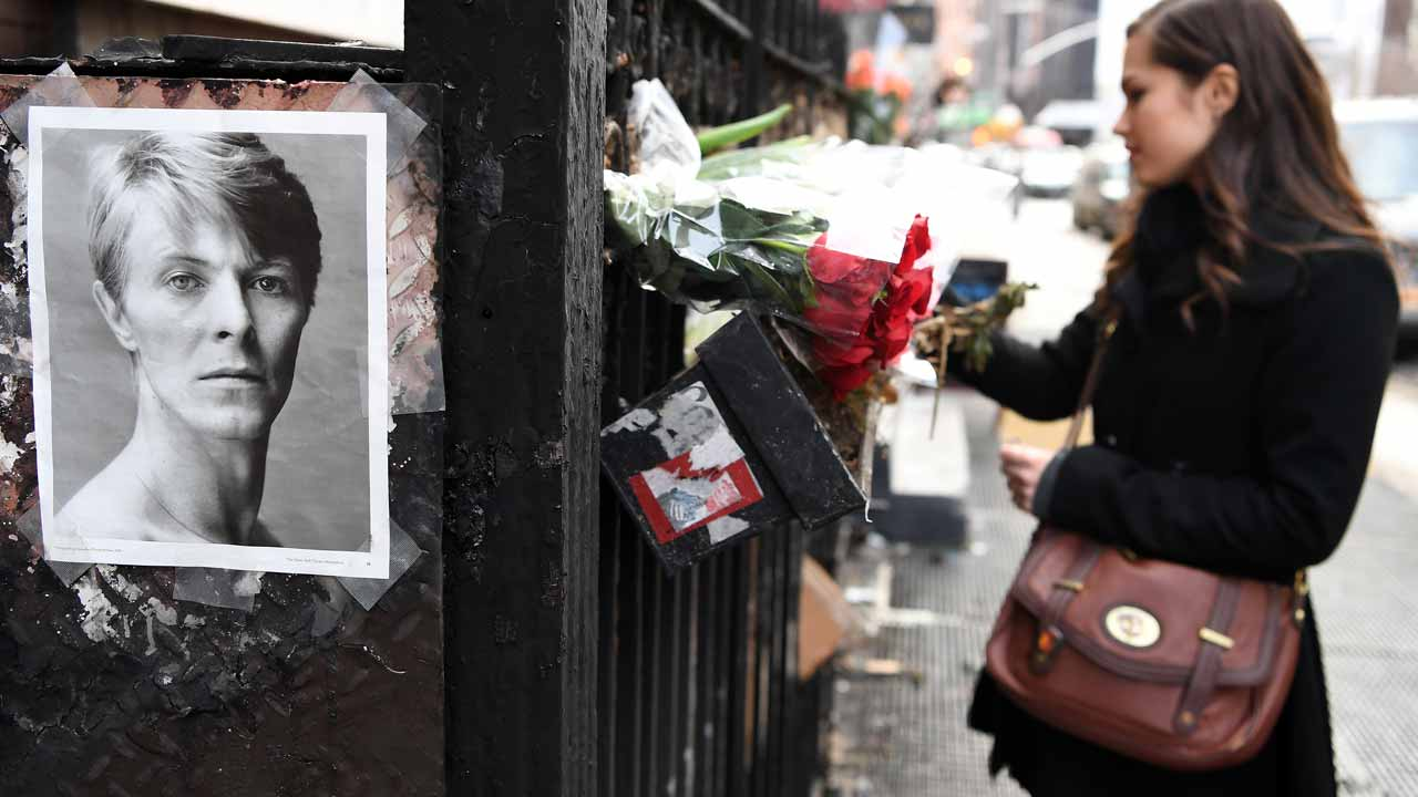 A woman places flowers outside of David Bowie's SoHo apartment building on the first anniversary of Bowie's death on January 10, 2017 in New York City. PHOTO: ANGELA WEISS / AFP