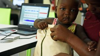 """Telecommunications engineer Olivia Koburongo fits a child with the mama-ope kit at the Makerere University of Public Health in Kampala on January 16, 2017. A team of Ugandan engineers has invented a """"smart jacket"""" that diagnoses pneumonia faster than a doctor, offering hope against a disease which kills more children worldwide than any other. ISAAC KASAMANI / AFP"""