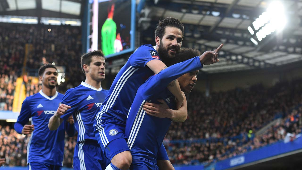 Chelsea's Brazilian midfielder Willian (R) celebrates with Chelsea's Spanish midfielder Cesc Fabregas (2R) on his back after scoring the opening goal during the English FA Cup fourth round football match between Chelsea and Brentford at Stamford Bridge in London on January 28, 2017. Glyn KIRK / AFP