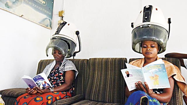 Women sitting under hair steamers read books from a mini-library at a hairdresser's in Abidjan                      (AFP Photo/Sia KAMBOU)