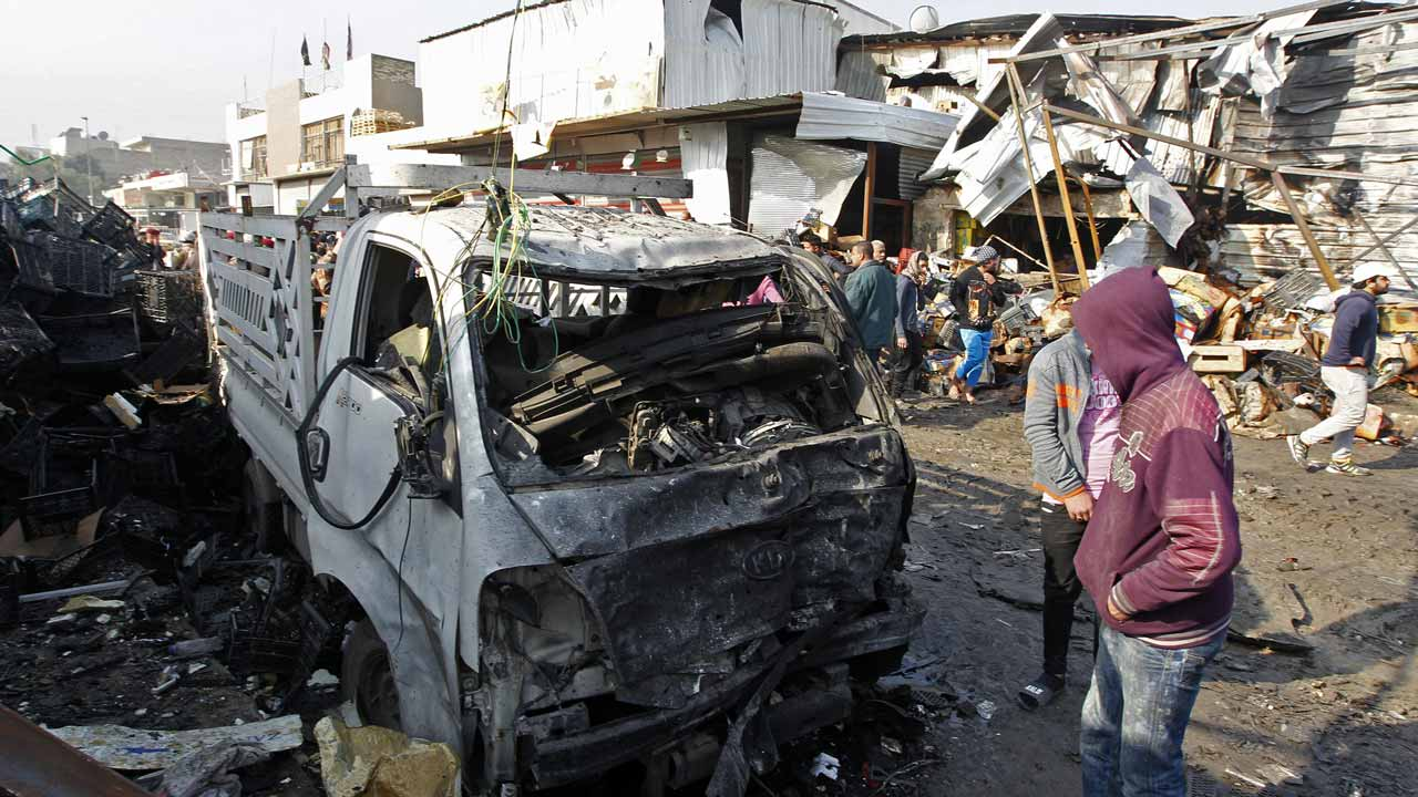 Iraqis inspect the site of an attack at Baghdad's main vegetable market on January 8, 2017. A suicide bomber blew up a car at the entrance of the market, killing at least 11 people and wounding dozens, security officials and medics said. SABAH ARAR / AFP