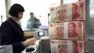 (FILES) This file photo taken on January 7, 2016 shows an employee counting 100-yuan (15 USD) banknotes at a bank in Lianyungang in eastern China's Jiangsu province. China said on December 29, 2016 it would almost double the number of foreign currencies it uses to determine the official value of the yuan, thereby diluting the role of the dollar. STR / AFP