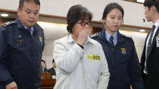 Choi Soon-Sil (C), the jailed confidante of disgraced South Korean President Park Geun-Hye, appears on the first day of her trial at the Seoul Central District Court in Seoul on January 5, 2017. Choi, the woman at the centre of a corruption scandal that triggered the biggest political crisis for a generation in South Korea, appeared in court on January 5 on fraud charges. / AFP PHOTO / POOL / Chung Sung-Jun