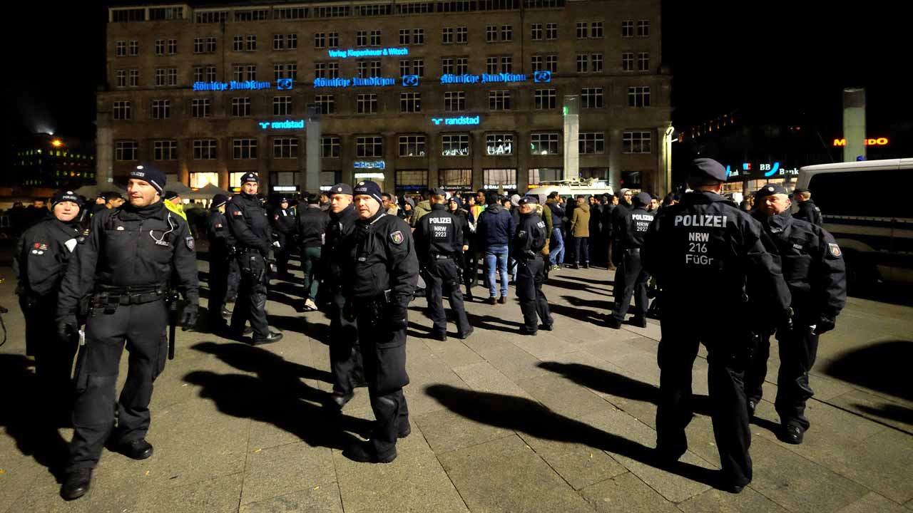 Policemen control visitors at the main train station in Cologne on December 31, 2016 during the New Year's eve. PATRIK STOLLARZ / AFP