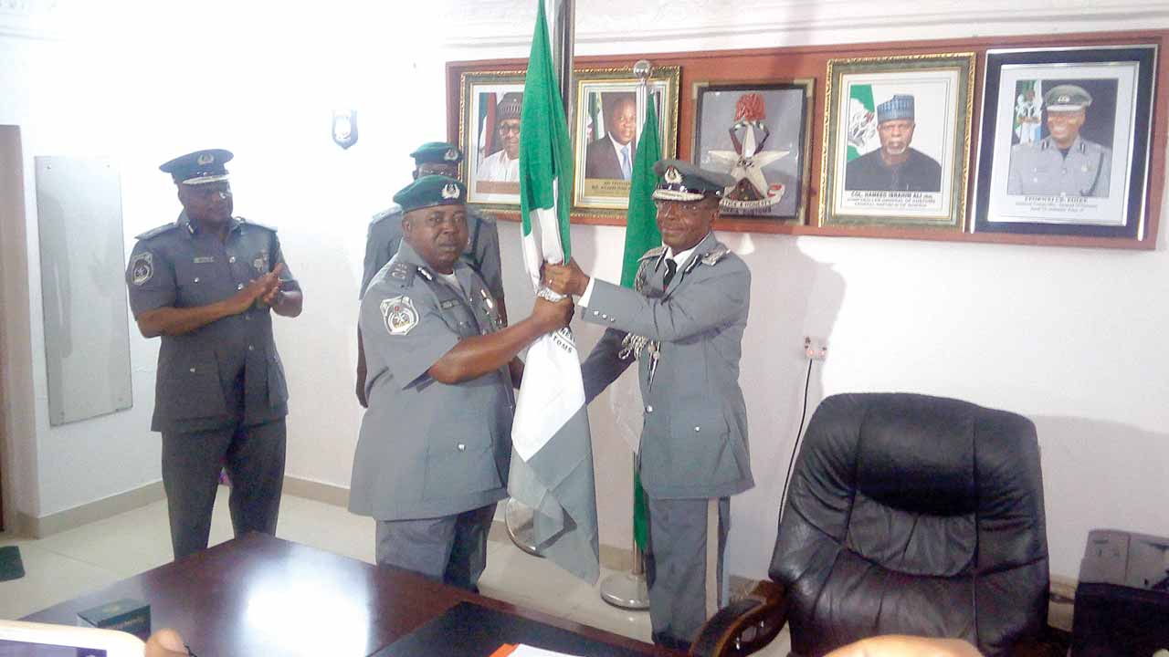 """Former Customs Zonal Coordinator, Zone """"A`, Assistant Comptroller-General Eporwei Edike (right); handling over the staff of office to the new Coordinator, Assistant Comptroller-General Monday Abueh at the Zone 'A' Command of the Nigerian Customs Service in Lagos."""