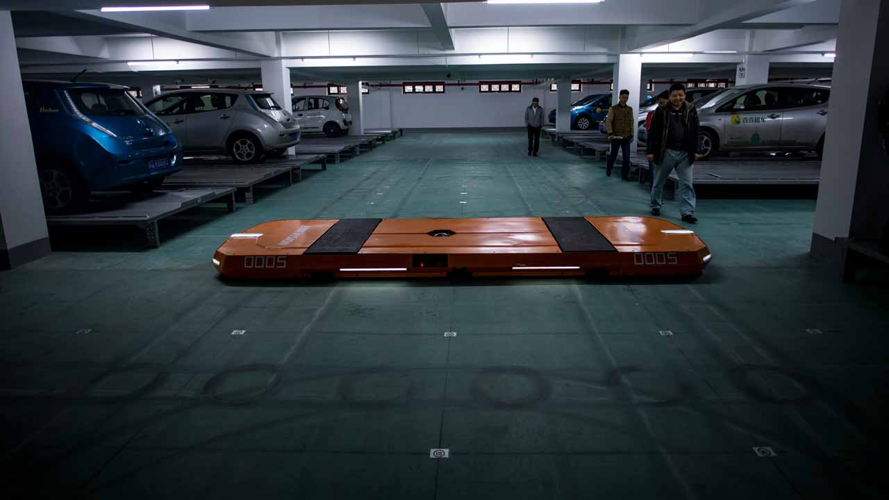 This picture taken on November 25, 2016 shows people watching a robotic unit of the smart parking system developed by Hikvision in a garage in Wuzhen Township of Tongxiang City, in east China's Zhejiang province. Flat, orange robots glide under stationary cars and ferry them to empty Chinese parking bays, using space more efficiently and, their creators say, reducing driver stress. Johannes EISELE / AFP