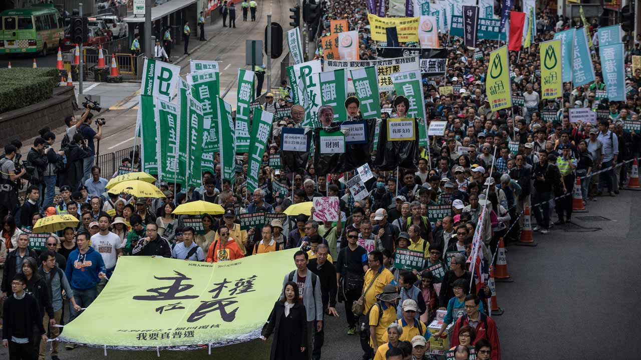 "Protesters including pro-democracy lawmakers Lau Siu-lai (bottom C), Edward Yiu (behind Lau) and Nathan Law (bottom L) carry a banner reading ""sovereignty belongs to the people"" during the annual new year's day rally in Hong Kong on January 1, 2017. Protesters marched to protest the government's bid to disqualify lawmakers as young campaigners grow increasingly frustrated with a lack of political reform. DALE DE LA REY / AFP"