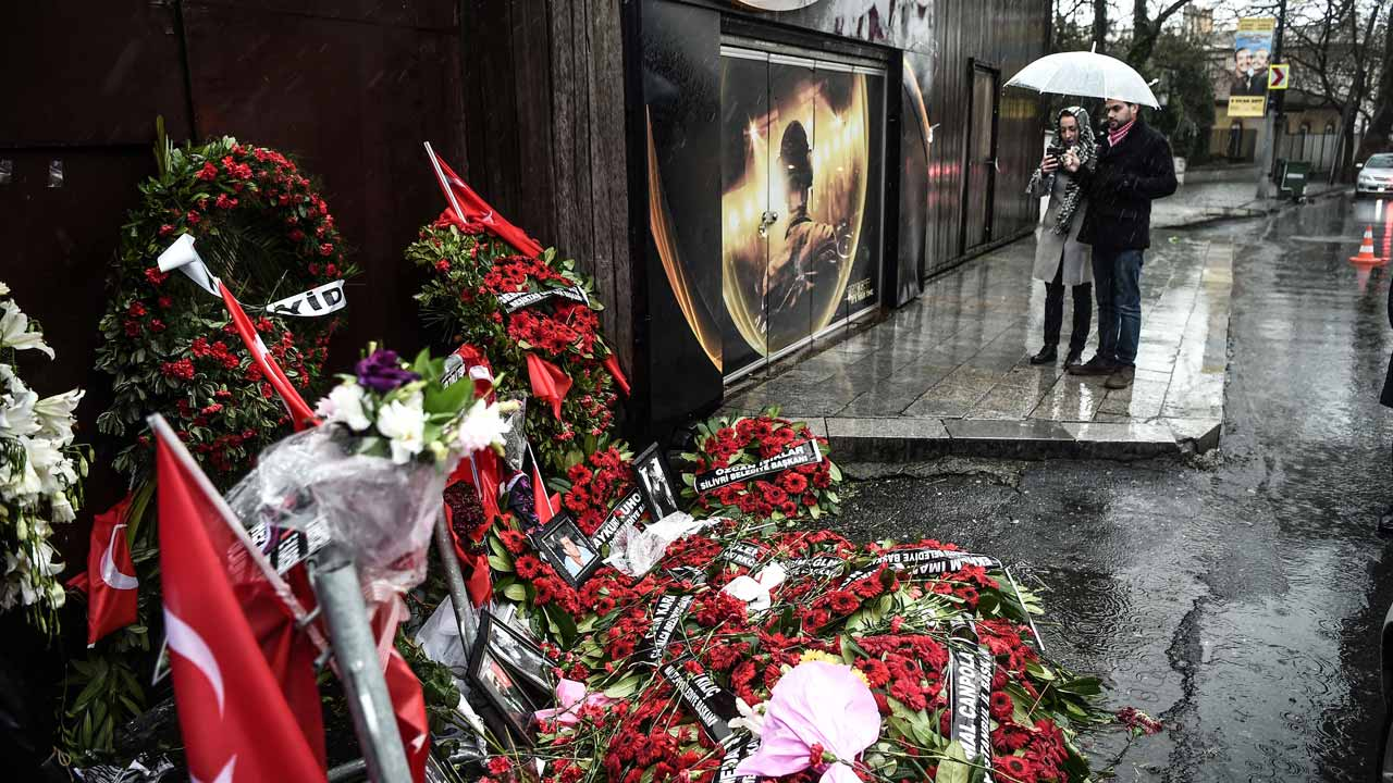 People take pictures of a makeshift memorial set in front of the Reina nightclub on January 5, 2017 in Istanbul, four days after a gunman killed 39 people on New Year's night. Elite Turkish police arrested several people today during fresh raids over the nightclub attack that killed 39, as authorities tightened Turkey's borders to prevent the fugitive killer from escaping. OZAN KOSE / AFP