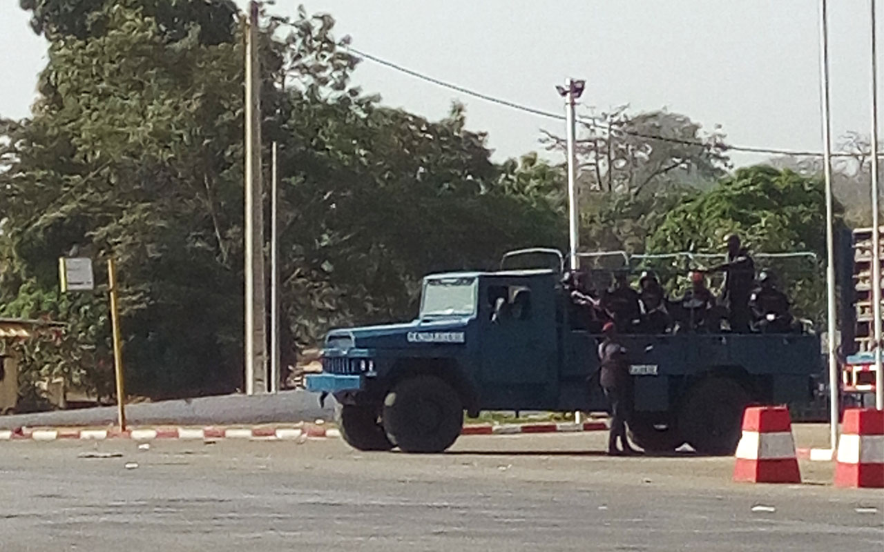 Ivorian gendarmes stand aboard a vehicle in a street of Bouake on January 6, 2017. Heavy weapons fire was heard on January 6 near Ivory Coast's largest military camp in the city of Bouake, where at least two police stations were attacked, an AFP journalist said. / AFP PHOTO / STR
