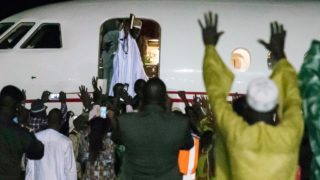 Former president Yaya Jammeh (C,up), the Gambia's leader for 22 years, waves from the plane as he leaves the country on 21 January 2017 in Banjul. Yahya Jammeh, the Gambia's leader for 22 years, flew out of the country on January 21, 2017 after declaring he would step down and hand power to President Adama Barrow, ending a political crisis. An AFP journalist at the airport saw Jammeh board an unmarked plane heading for an unspecified destination, seen off by a delegation of dignitaries and soldiers. STRINGER / AFP