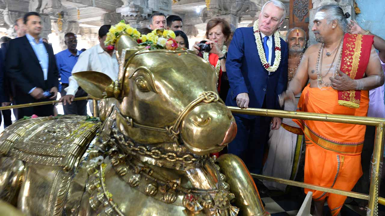 French Minister of Foreign, Affairs and International Development Jean-Marc Ayrault (2R), speaks with a Hindu priest alongside a brass sculpture of the sacred bull 'Nandi' during a visit to the Someshwara Temple in the Indian city of Bangalore on January 8, 2017.  MANJUNATH KIRAN / AFP