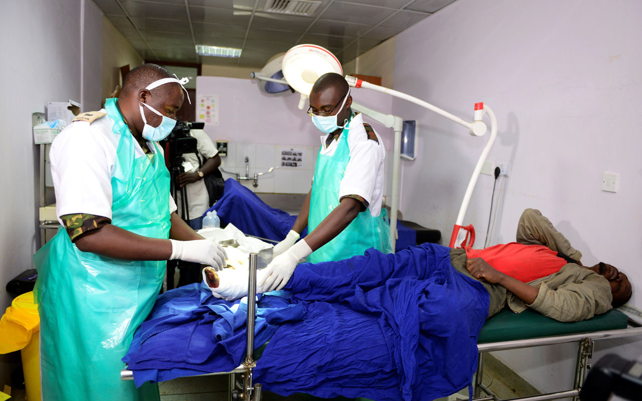 """(FILES) This file photo taken on December 10, 2016 shows Kenyan Defence force (KDF) doctors attending to an injured man at Kenyatta National Hospital in Nairobi. A Kenyan court has handed down a one-month suspended jail term to seven union officials over a doctors' strike which has crippled public hospitals for the last 40 days. However Judge Hellen Wasilwa said that if the doctors did not call off the strike within two weeks, the officials would """"be arrested and taken to jail."""" / AFP PHOTO / JOHN MUCHUCHA"""