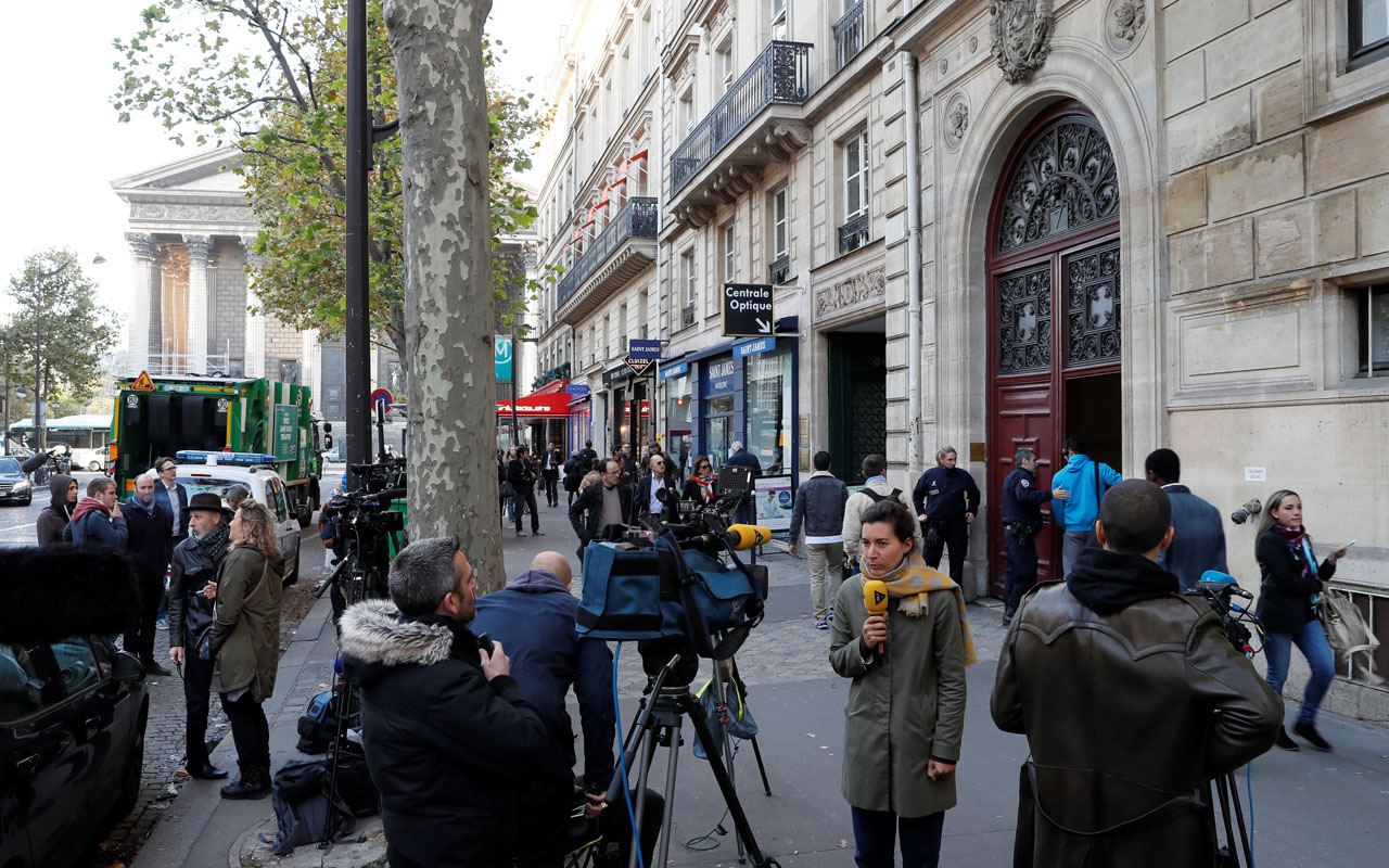 (FILES) This file photo taken at the Rue Tronchet, near Madeleine, central Paris, on October 3, 2016 shows journalists working as police officers stand guard at the entrance to a hotel residence, where US reality television star Kim Kardashian was robbed at gunpoint by assailants disguised as police who made off with millions, mainly in jewellery. 16 people were arrested over Kardashian Paris robbery according police source, AFP reported on January 9, 2017. Kardashian was tied up and robbed of jewellery worth around nine million euros ($9.5 million) when a gang of masked men burst into the luxury Paris residence where she was staying during Fashion Week in October. / AFP PHOTO / Thomas SAMSON