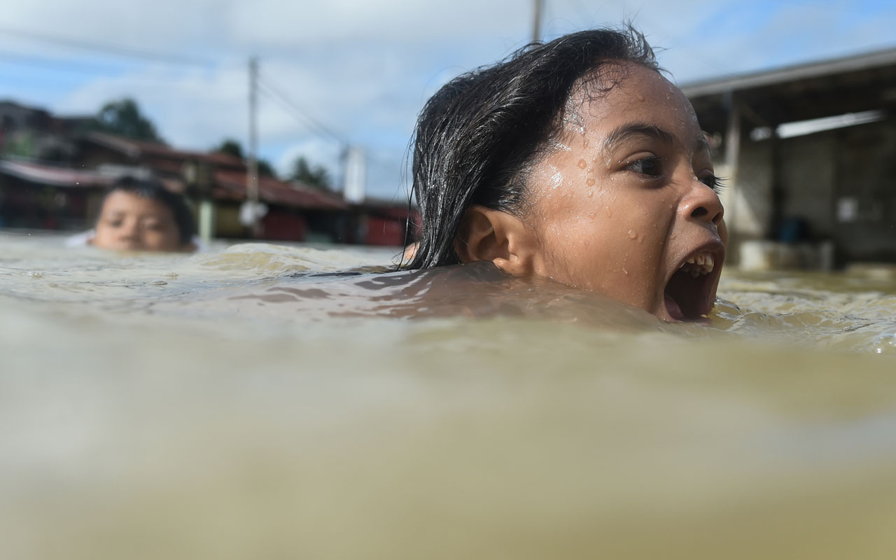 Children swim in floodwaters in Malaysia's northeastern town of Rantau Panjang, which borders Thailand, on January 5, 2017. Floods in two northeast Malaysian states have now forced almost 23,000 people from their homes and extra relief centres have been opened, rescue officials said January 4. / AFP PHOTO / Mohd RASFAN
