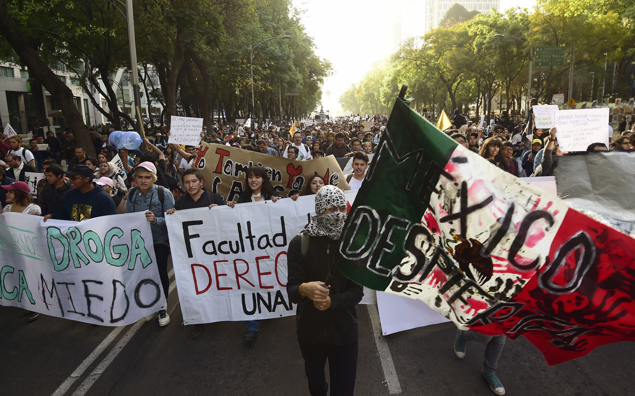 People march to demand the resignation of President Enrique Pena Nieto, after he did not signal any backpedaling on the government's unpopular decision to increase gasoline prices by up to 20.1 percent in Mexico City on January 9, 2017. Violent demonstrations and looting in Mexico over the sharp increase in gasoline prices left three people dead and more than 1,500 under arrest, the government said Friday, while giving assurances that gas stations are operating almost normally again. / AFP PHOTO / Alfredo ESTRELLA