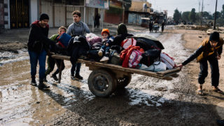 Iraqis pull a cart with their belongings in a street in Mosul's al-Zahraa neighbourhood on January 8, 2017, as they flee with other civilians during an ongoing military operation against Islamic State (IS) group militants. Elite Iraqi forces battling the Islamic State group in eastern Mosul reached the Tigris River that splits the city in two for the first time, a spokesman said.  Dimitar DILKOFF / AFP
