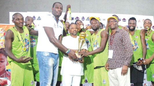 President, Olumide Oyedeji Youth Foundation, Mr. Olumide Oyedeji, Director of Grassroots Sports, Lagos State Sports Commission, Dr. Are and Managing Director, Honeywell Flour Mills Plc, Mr. Lanre Jaiyeola presenting the cup to winner of the Olumide Oyedeji Intercollegiate Basketball Championship, Team Ahmadu Bello University, in Lagos… on Saturday.