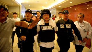 Police officer Ricky Sta. Isabel (C), one of the suspects in the kidnapping and murder of South Korean businessman Jee Ick Joo, is escorted by fellow policemen as they leave the National Bureau of Investigation (NBI) building in Manila on January 20, 2016. A South Korean businessman kidnapped by Philippine policemen under the guise of a raid on illegal drugs was murdered at the national police headquarters in Manila, authorities said Thursday. NOEL CELIS / AFP