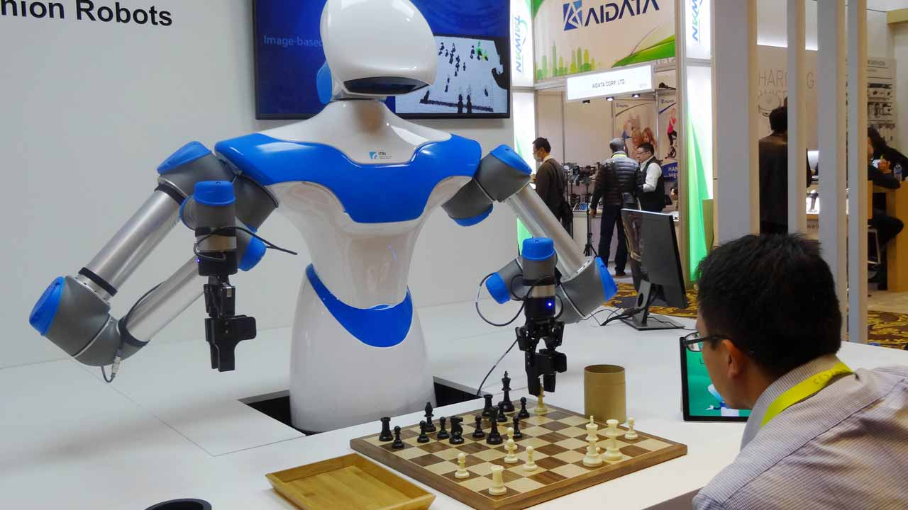 """A robot developed by Taiwan engineers moves chess pieces on a board against an opponent, ,at the 2017 Consumer Electronic Show (CES) in Las Vegas, Nevada on January 8, 2017. The robot developed by Taiwan's Industrial Technology Research Institute, which spent the week playing games against opponents at the Consumer Electronics Show, was displaying what developers call an """"intelligent vision system"""" which can see its environment and act with greater precision than its peers. Rob Lever / AFP"""