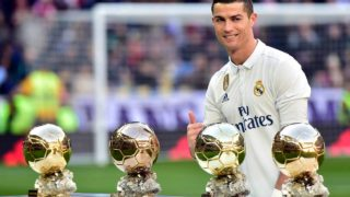 Real Madrid's Portuguese forward Cristiano Ronaldo poses with his four Ballon d'Or France Football trophies before the Spanish league football match Real Madrid CF vs Granada FC at the Santiago Bernabeu stadium in Madrid on January 7, 2017.  GERARD JULIEN / AFP