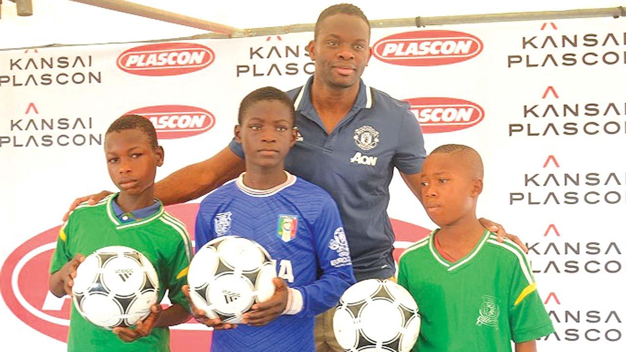 Former Manchester United striker Louis Saha with pupils of St John's Catholic Primary School, Bolade, Oshodi, Lagos during Kansai Plascon schools Community Social Responsibilities (CSR) yesterday.