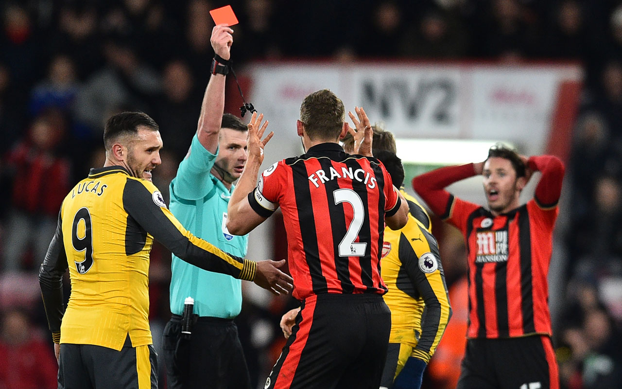 Referee Michael Oliver shows a red card to Bournemouth's English defender Simon Francis (C) for a poor tackle during the English Premier League football match between Bournemouth and Arsenal at the Vitality Stadium in Bournemouth, southern England on January 3, 2017. / AFP PHOTO / Glyn KIRK /