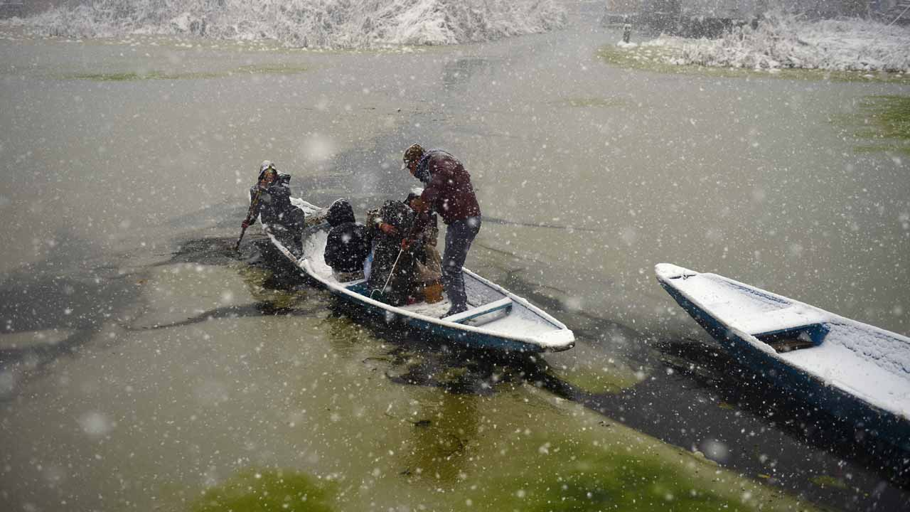 An Indian Kashmiri boatman transports passengers during heavy snowfall on Dal Lake in Srinagar on January 6, 2017. Indian-administered Kashmir has been cut off from the rest of the country after heavy snowfall closing the 294km Jammu-Srinagar national highway, the only road link between Kashmir and rest of the country. TAUSEEF MUSTAFA / AFP