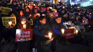 Protesters attend a candle-lit rally calling for South Korean President Park Geun-Hye's immediate departure from her office, in downtown Seoul on December 31, 2016. South Korea sees in the new year with a massive protest calling for an immediate arrest of impeached President Park Geun-Hye. JUNG Yeon-Je / AFP AFP / AFP